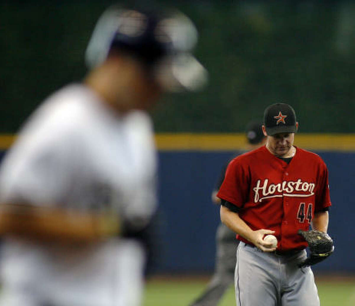 Astros starting pitcher Roy Oswalt, right, looks down at the ball after giving up a two-run home run to Milwaukee Brewers' Ryan Braun, left, in the first inning.