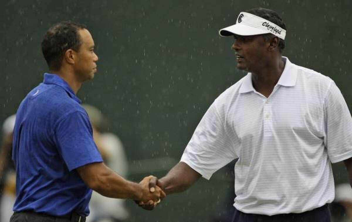 Woods, left, shakes hands with Vijay Singh on the 18th green following their third round. Singh shot a 75 in Round 3 to fall to even par for the tourney. He opened with a 69 on Thursday.