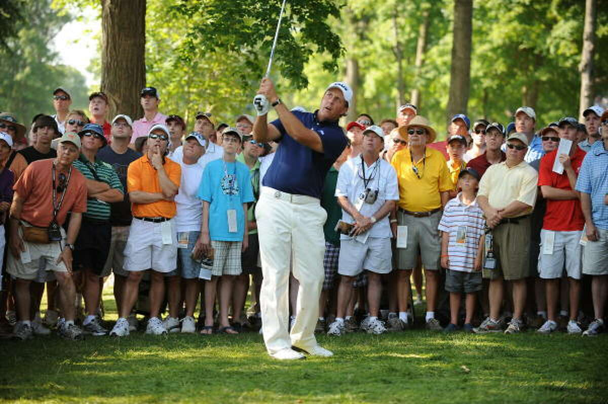 The gallery watches as Phil Mickelson plays a shot from the rough on the 14th hole.