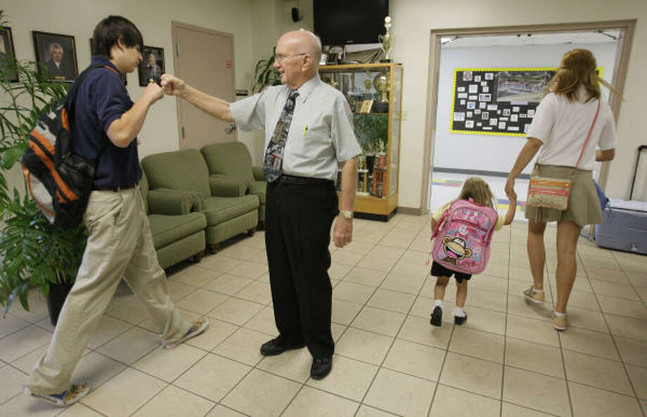 "School chaplain Robert Farrar known as ""Doc""  greets Tyler Pickard, 14, left,  a sophomore, on the first day of class at Westbury Christian on Aug. 13. Photo: Melissa Phillip, Chronicle"