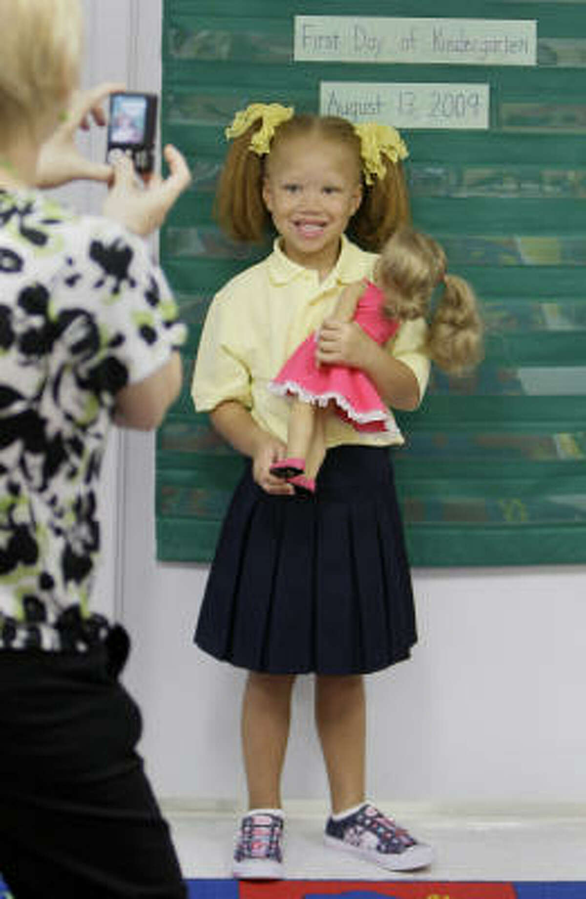 Kendall Wyatt, 5, holding her doll, Sarah, has her photo taken by teacher Gereta Semanek on the first day of kindergarten at Westbury Christian.