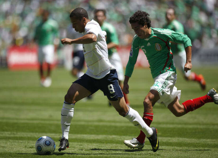 Charles Davies, left, of the US soccer team, controls the ball before scoring as Efrain Juarez of Mexico chases him. Photo: Claudio Cruz, AP