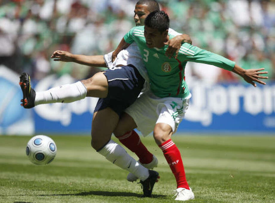 Charlie Davies, left, of the United States, fights for the ball with Carlos Salcido of Mexico. Photo: Claudio Cruz, AP