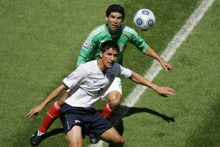 The Dynamo's Brian Ching of the United States holds off Jonny Magallon. Photo: Miguel Tovar, AP