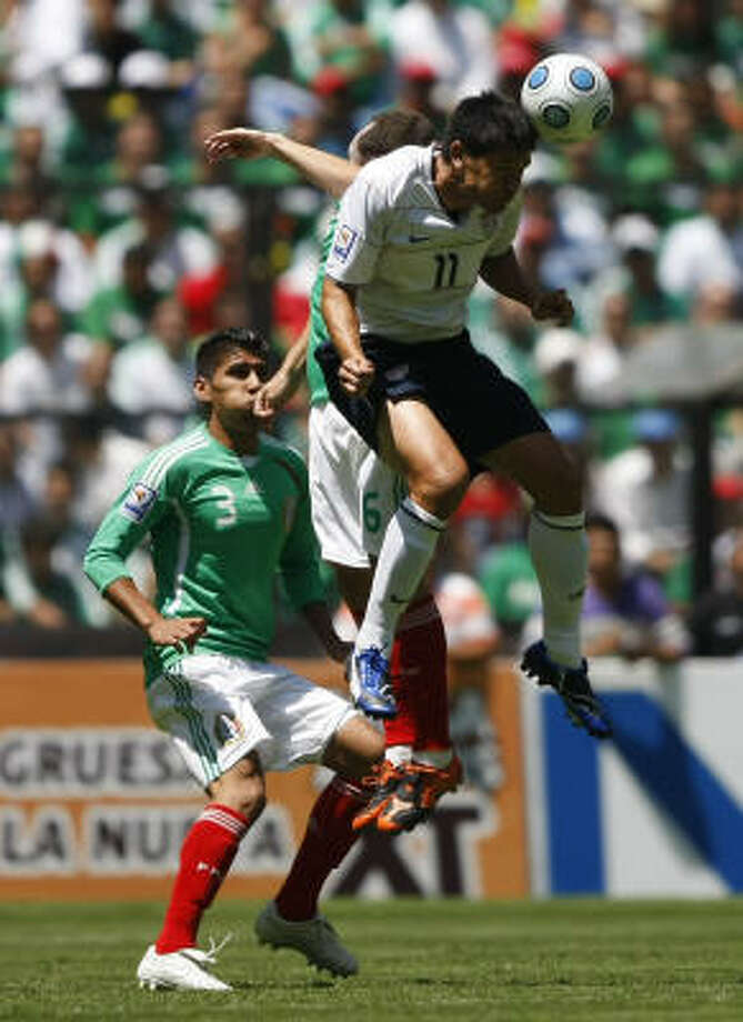 Dynamo's own Brian Ching, right, of the U.S. national soccer team, fights to head the ball against Gerardo Torrado and Carlos Salcido, left, of the Mexico team. Photo: Dario Lopez-Mills, AP