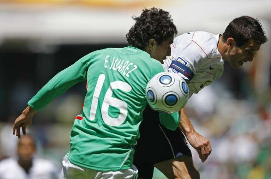 Carlos Bocanegra, right, of the U.S. national soccer team, fights to head the ball against Efrain Juarez of Mexico. Photo: AP