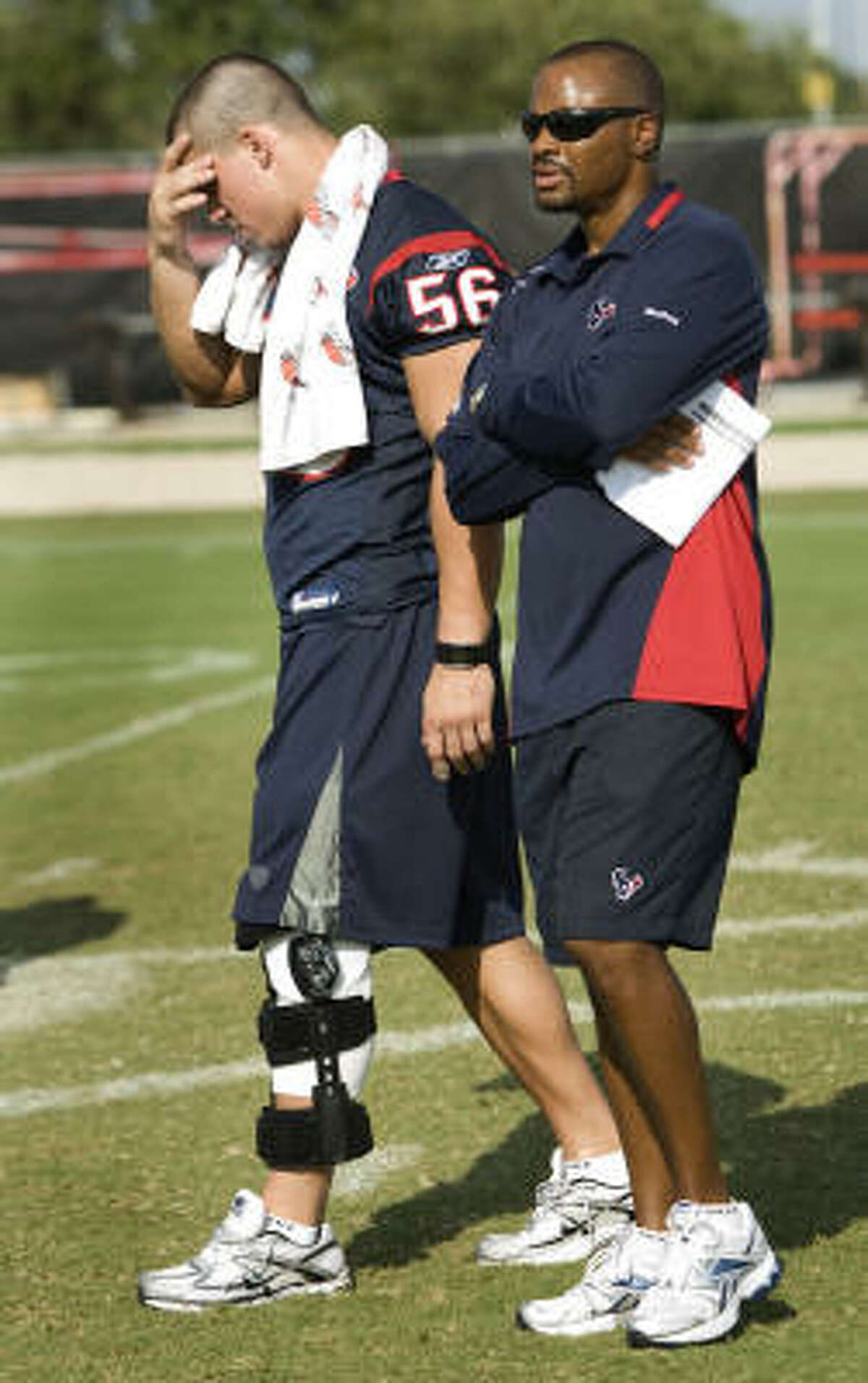 Brian Cushing walks with general manager Rick Smith at the end of practice.