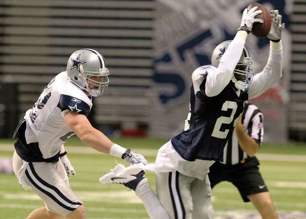 Safety Abram Elam (24) picks off a pass against tight end Jason Witten (left) during the afternoon session of the Dallas Cowboys training camp at the Alamodome on Saturday, Aug. 6, 2011. Kin Man Hui/kmhui@express-news.net Photo: KIN MAN HUI, -- / SAN ANTONIO EXPRESS-NEWS