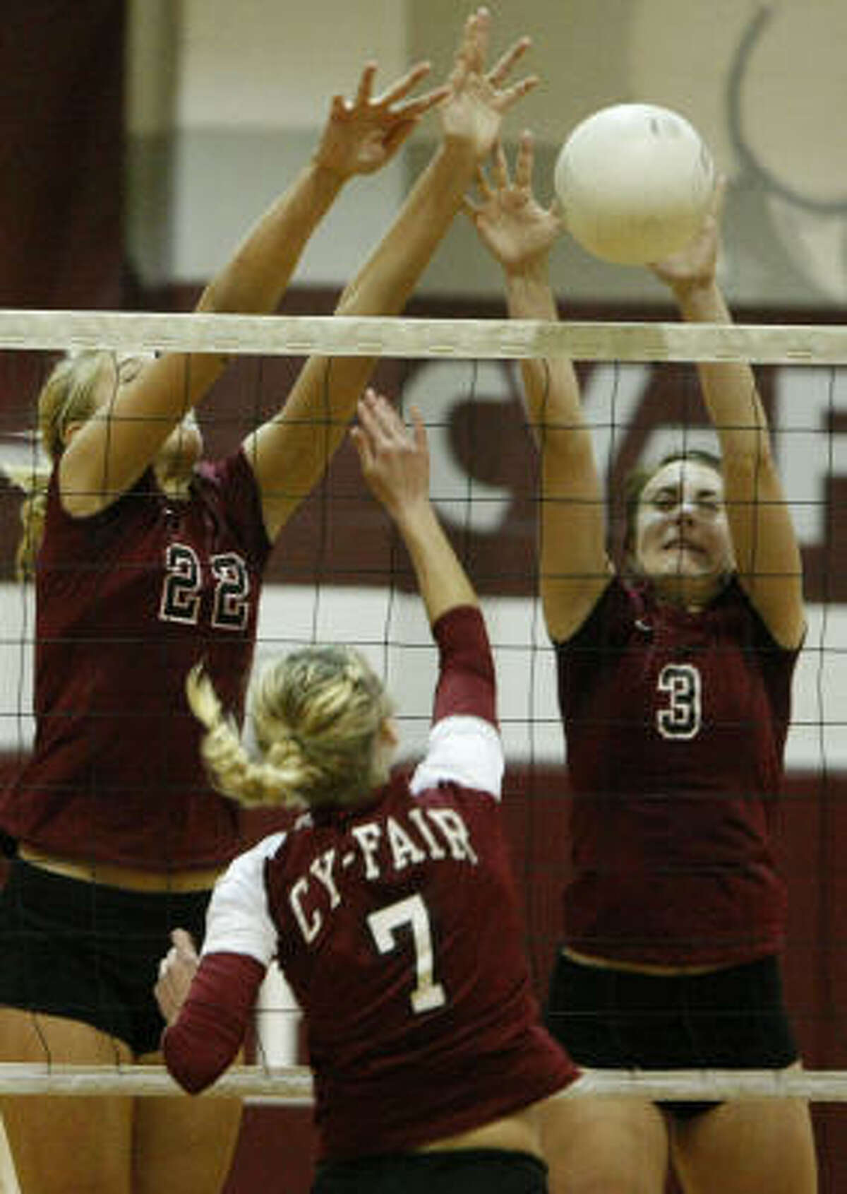 Cougars Rachel Fairbanks (3) and Jennifer Sanders (22) jump to block a spike from Cy-Fair's Audra Vaello.