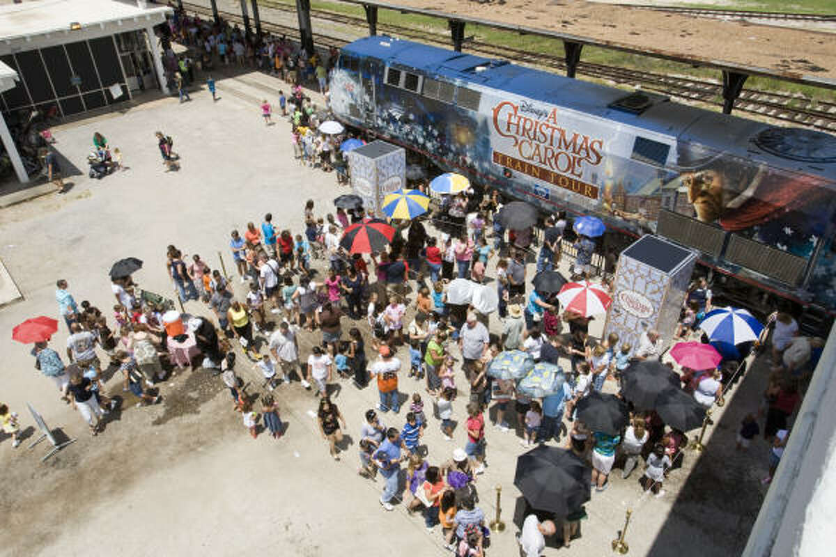 Visitors line up outside a special Amtrak train as they wait to tour Disney's A Christmas Carol train in Houston.