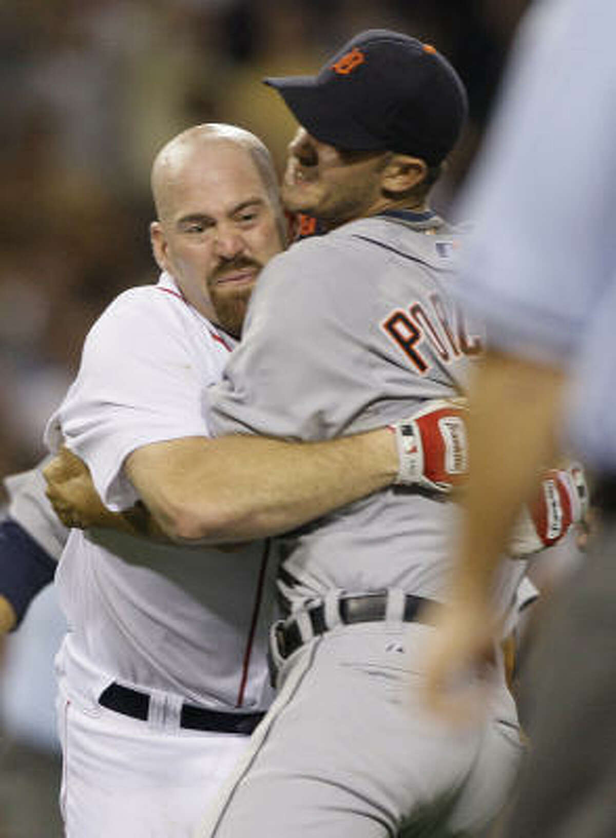 The Red Sox' Kevin Youkilis, left, wrestles with Tigers' starter Rick Porcello after being hit by a pitch in the second inning. Youkilis had been hit in Monday's game as well.