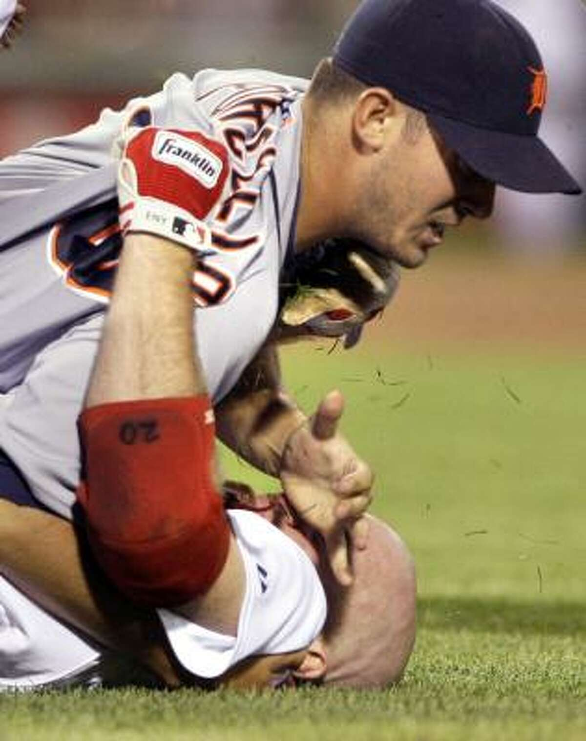 The Tigers' Rick Porcello, top, wrestles with Red Sox first baseman Kevin Youkilis after Youkilis charged the mound and tackled Porcello.