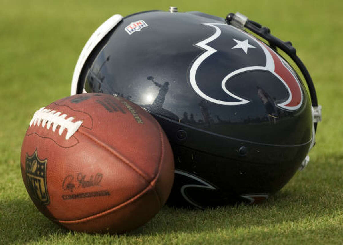 The silhouette of Texans punter Matt Turk is reflected on his helmet as he warms up on the sidelines.
