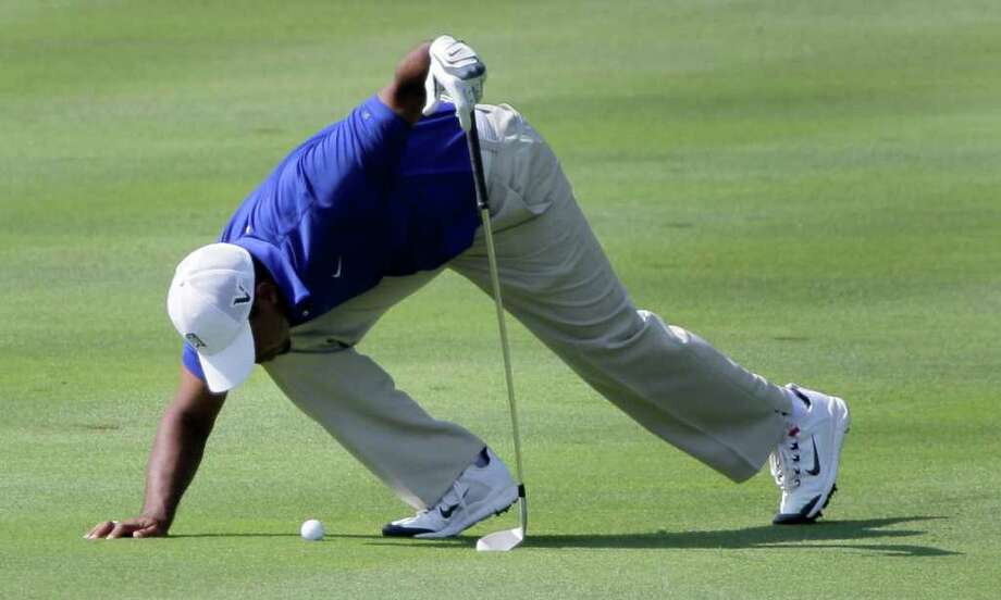 Tiger Woods looks over the lie of his ball in the 16th fairway during third round play in the Bridgestone Invitational golf tournament at Firestone Country Club in Akron, Ohio on Saturday, Aug. 6, 2011. (AP Photo/Amy Sancetta) Photo: Amy Sancetta, STF / AP