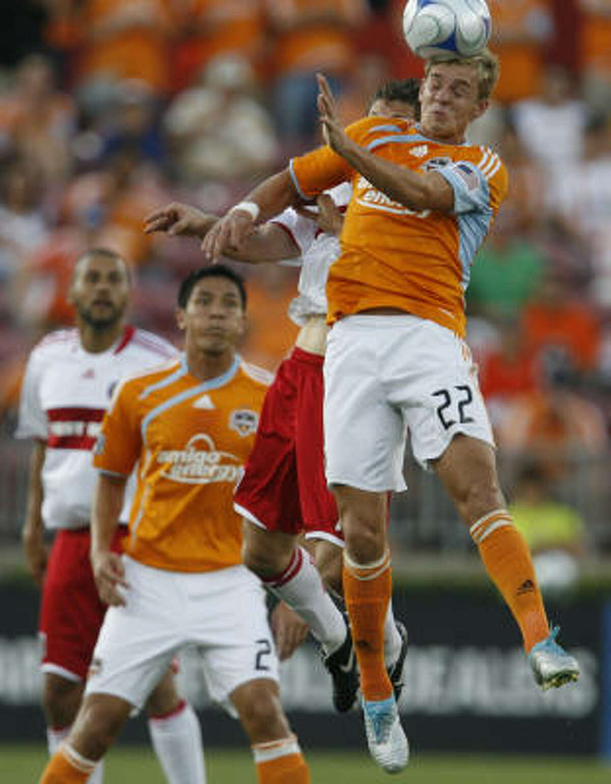 Dynamo midfielder Stuart Holden, front, goes up for the ball against Chicago Fire midfielder Logan Pause during the first half.