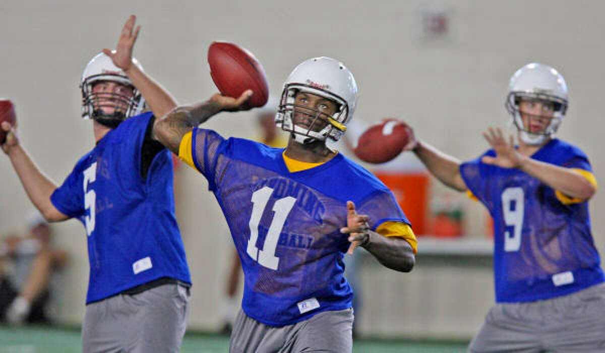 Wyoming quarterback Robert Benjamin (11) goes through passing drills with teammates Austyn Carta-Samuels, left, and Dax Crum during practice Thursday in Laramie, Wyo. The Longhorns open with Louisiana-Monroe on Sept. 5, then play at Wyoming on Sept. 12.
