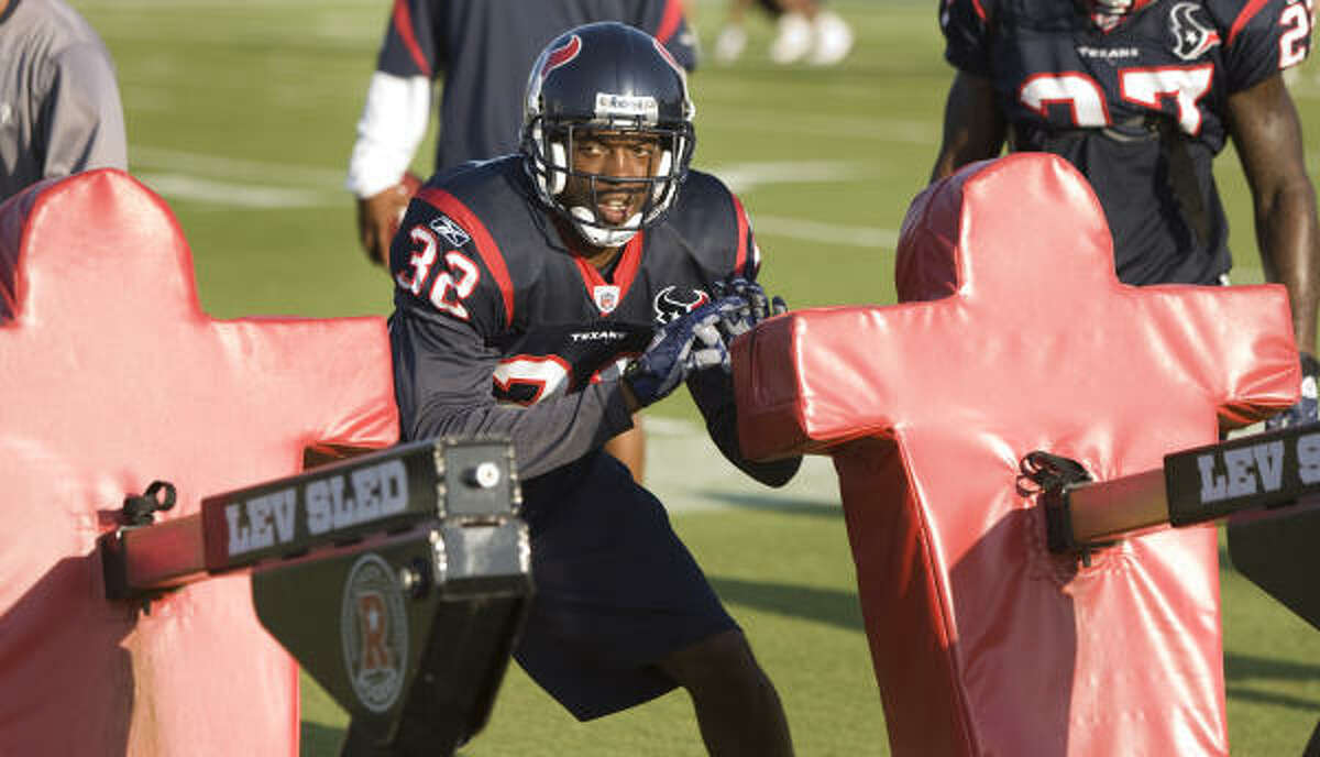 Texans cornerback Fred Bennett hits the blocking sled during a drill.