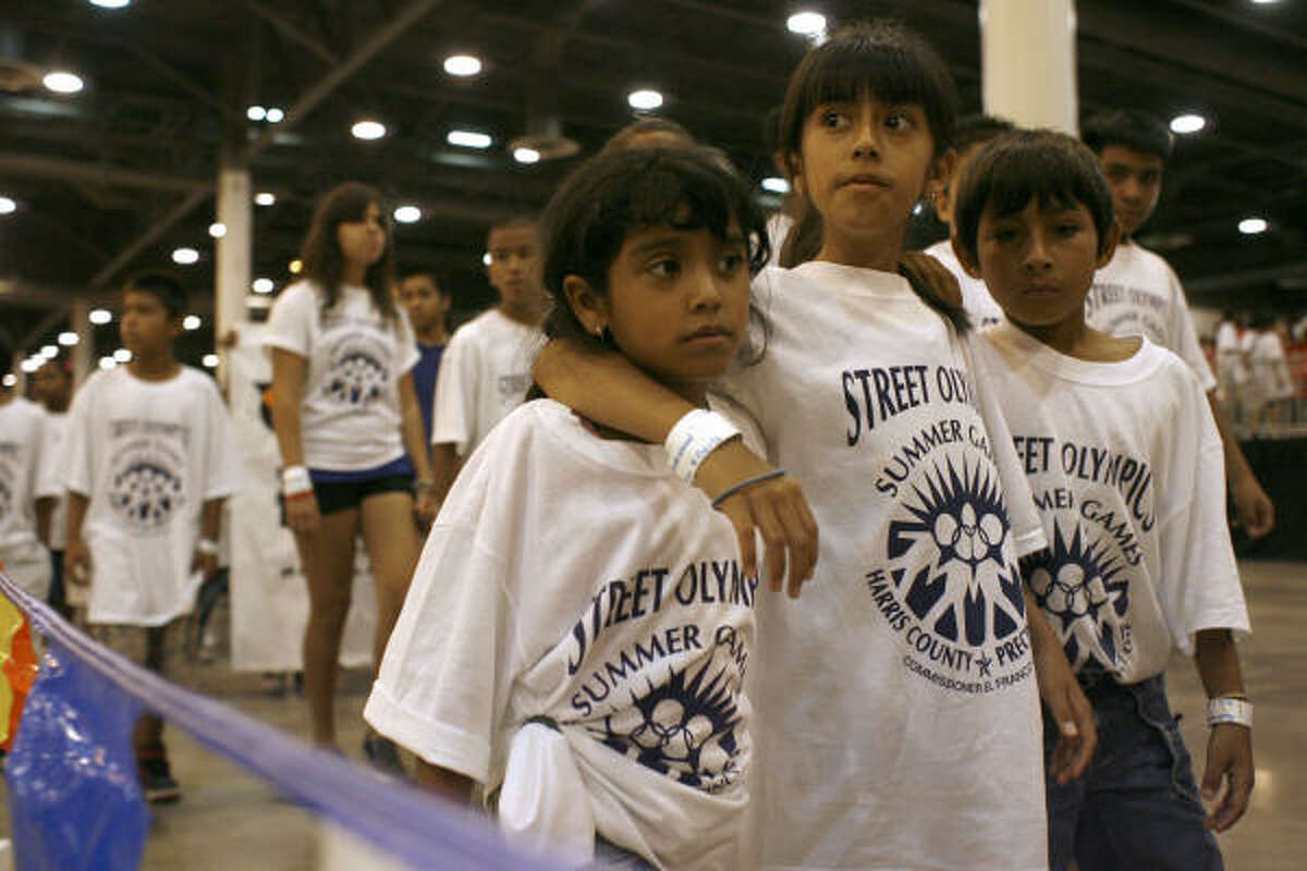 A group of children walk in the parade to start the 23rd annual Harris County Street Olympics in Reliant Center. The opening ceremony included a parade of the children competing in the street olympics games and music performed by the Willowridge Eagles Marching Band.