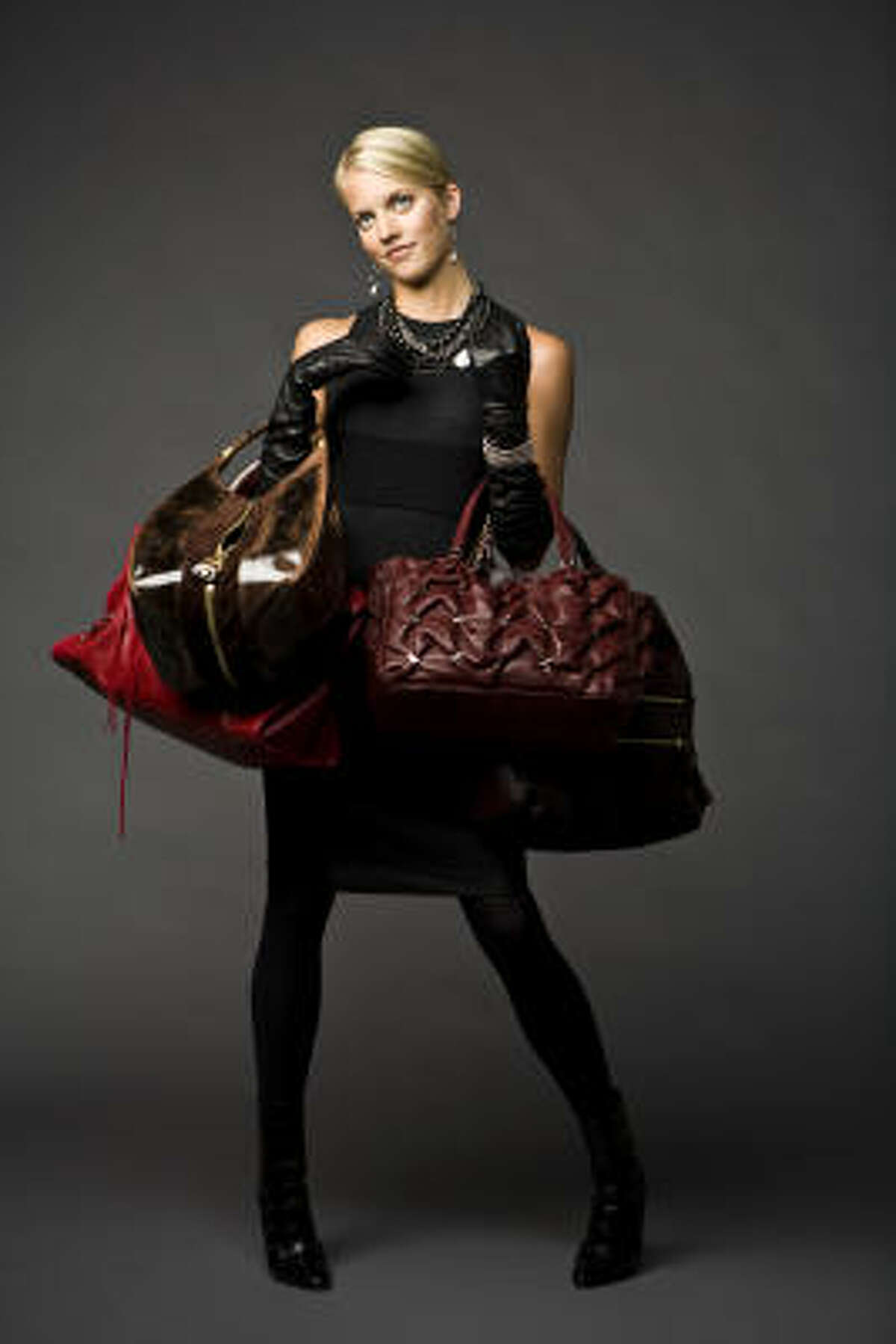 From left: Balenciaga's red carry-all, $1,595, Neiman Marcus; Jimmy Choo's Middle Zip hobo, $1,450, Saks Fifth Avenue; Ferragamo's red leather tote with metal vara buckle details $1,890, similar styles at Ferragamo boutique; and Coach's Cambridge leather large hobo, $568, Coach. Vince dress, $295, and Manolo Blahnick black booties, $1,165, Neiman Marcus. Gloves are stylist's own. Earrings, necklace and bracelet, $29.50-$79.50, Banana Republic.