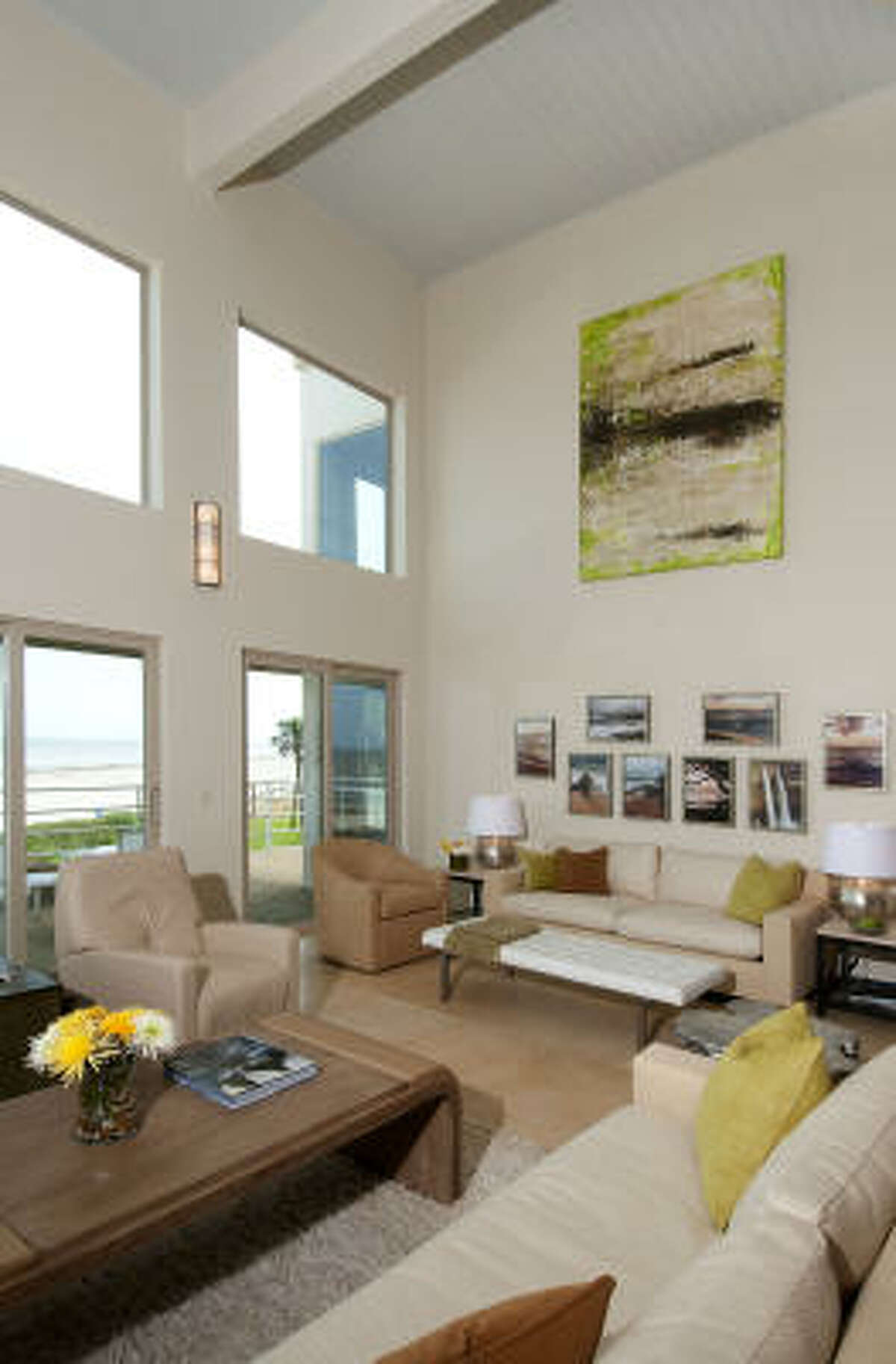 The living room's light-colored walls, floors and furnishings don't distract from the beautiful beach environment. The large-scale painting, Aquarela Verde by Mario Sergio, is from Cantoni.