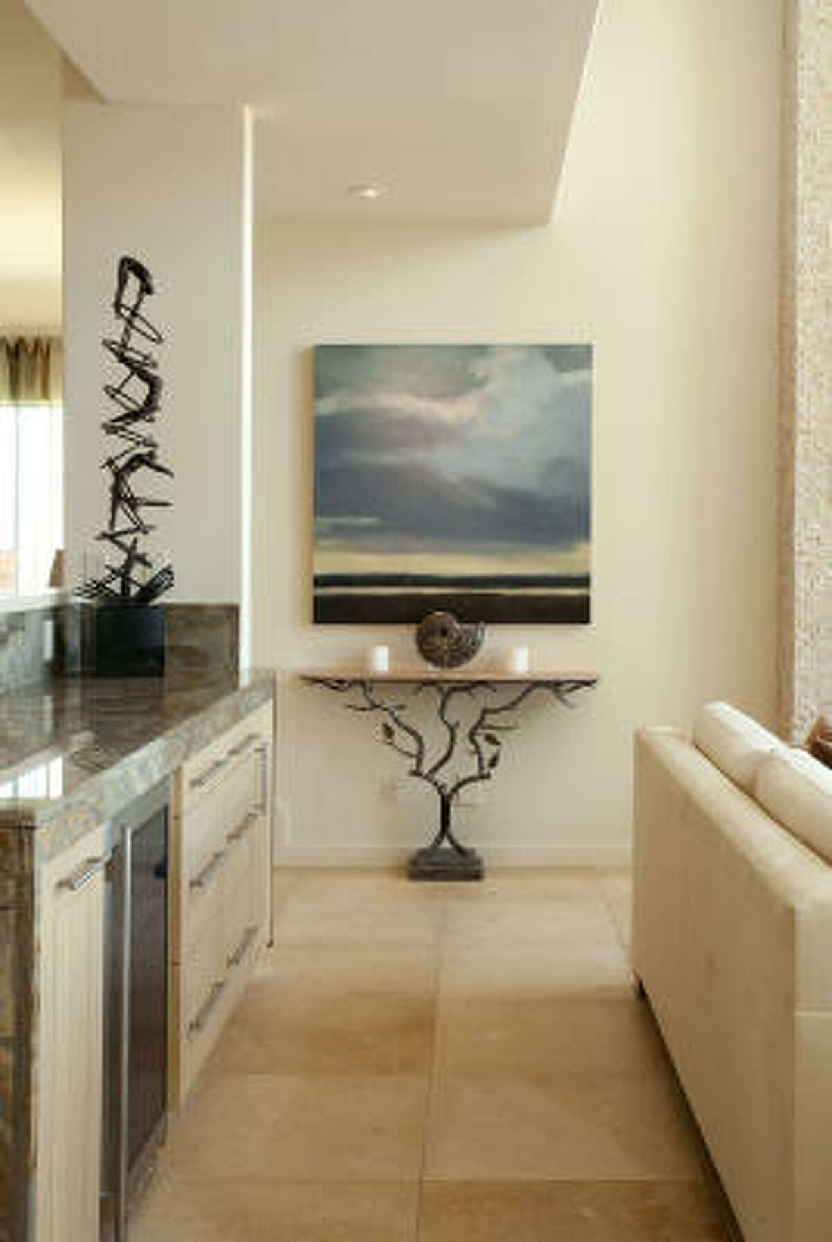Slovack selected a moody painting from Thornwood Gallery, Gathering Storm by Kim Coulter, to contrast with the brightness of the beach. The custom console table has a patinated steel base and travertine stone top.