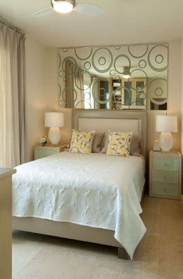 Large mirrors from Cantoni make a cozy guest bedroom feel bigger and brighter. At certain angles, you can see a reflection of the beach and ocean in the mirrors. Photo: Don Glentzer