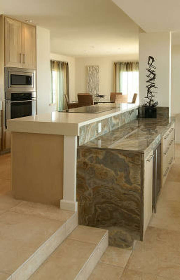 "Savanna granite from Africa tops this bar between the kitchen and living room. Slovack says the pattern ""looks like the water and sand mixed together."" Photo: Don Glentzer"
