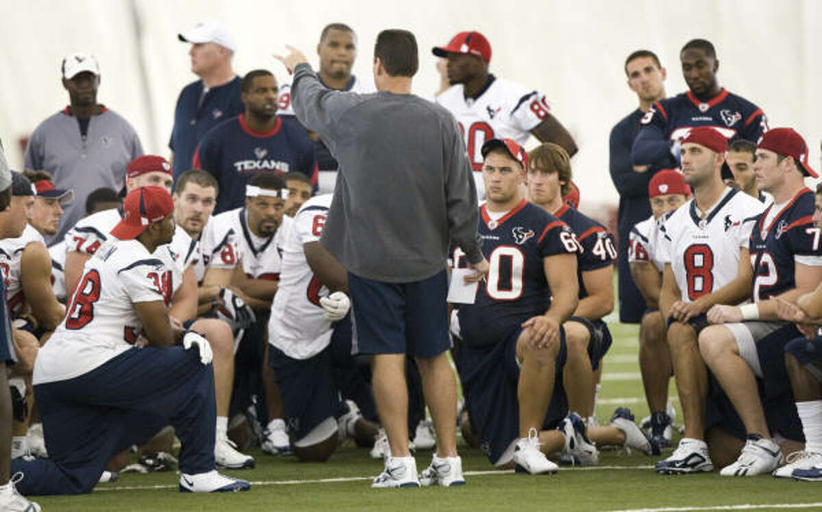 Texans coach Gary Kubiak is surrounded by his team at the end of practice.