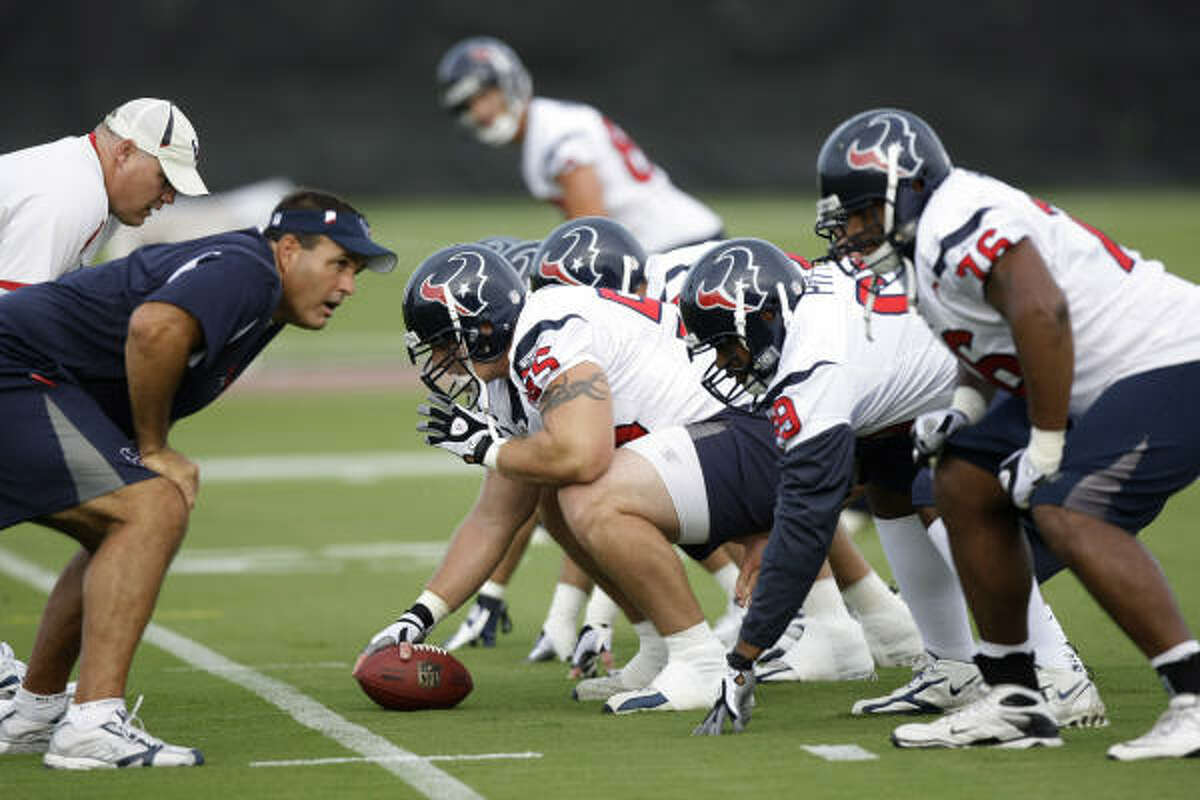 Texans offensive assistant Bruce Matthews, left, lines up over center Chris Myers (55), Chester Pitts (69) and Duane Brown (76) during a drill.