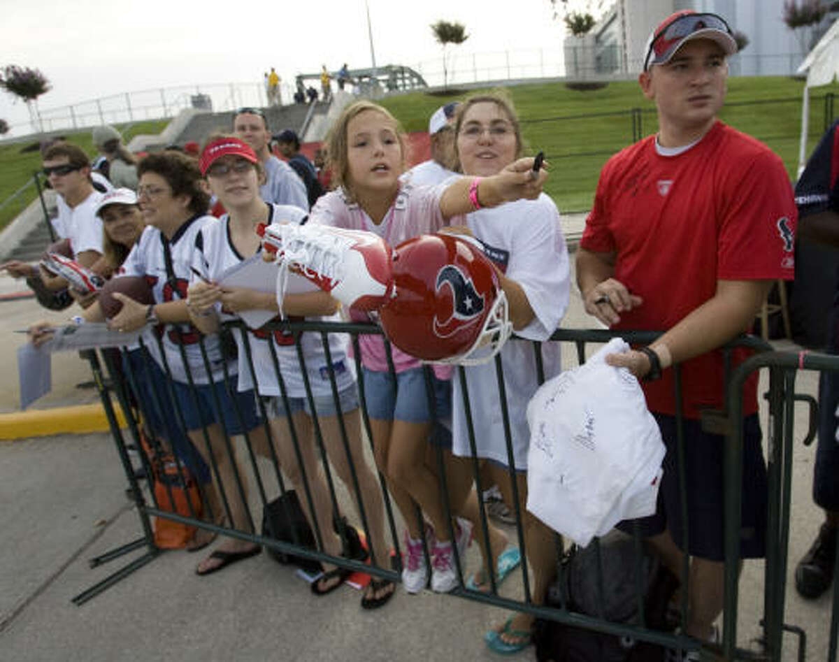 Texans fans line up to seek autographs before the opening practice of training camp.