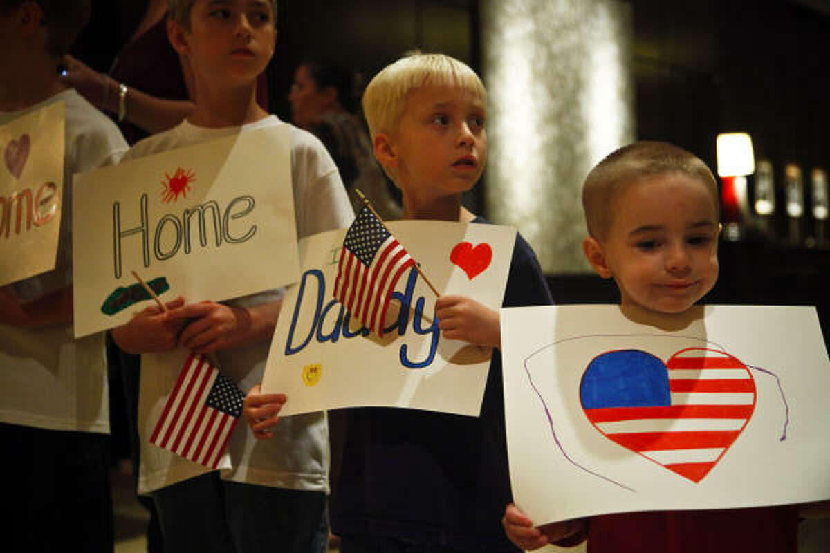 Luke, John Michael and Levi Hollon hold signs to welcome home their father, James Hollon, as local soldiers from the 712th Military Police Company, Combat Support, of the Texas National Guard return home from an Iraq deployment. Read the story