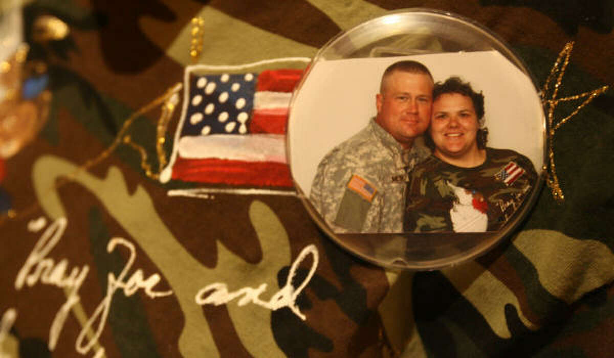 Family members wear buttons of their loved ones while waiting for the arrival of the 712th Military Police Company, Combat Support, of the Texas National Guard based in Baytown.