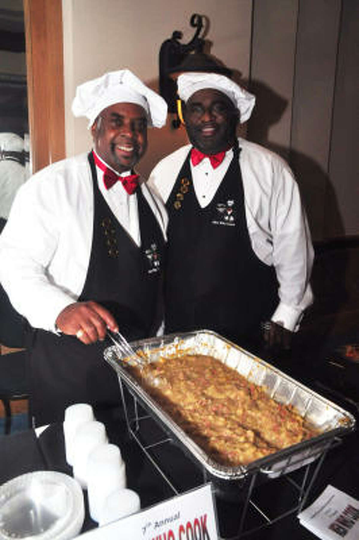 James Jones and Marlon Brown show off their food at the League City Chamber of Commerce's Men Who Cook event at South Shore Harbour Resort in League City.