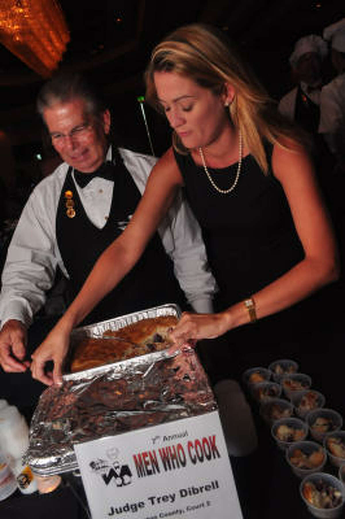 Careen Plummer helps Judge Trey Dibrell with his Hawaiian Surprise dessert.