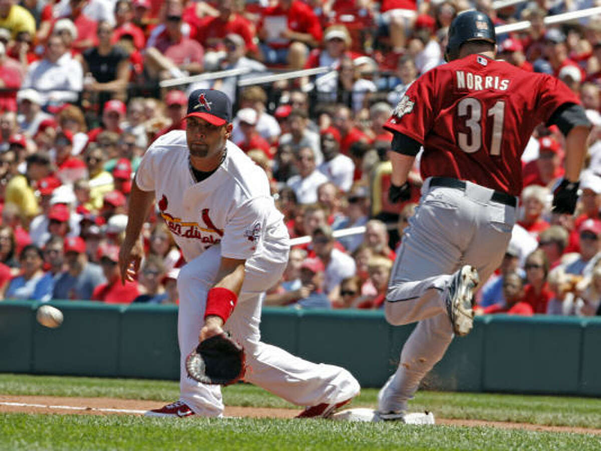 Astros starter Bud Norris reaches first safely for his first major league hit as Cardinals first baseman Albert Pujols waits on the throw in the third inning.