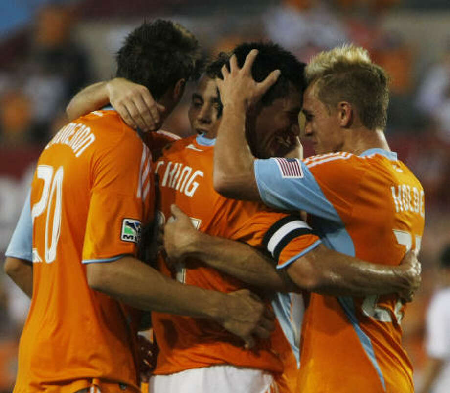 Aug. 1: Dynamo 4, D.C. 3Houston Dynamo forward Brian Ching, center, is hugged by Stuart Holden, right, Geoff Cameron, left, and Brad Davis after scoring the team's second goal. The Dynamo scored three goals in four minutes during the first en route to a 4-3 win over D.C. United on Saturday at Robertson Stadium in Houston. Photo: Julio Cortez, Chronicle