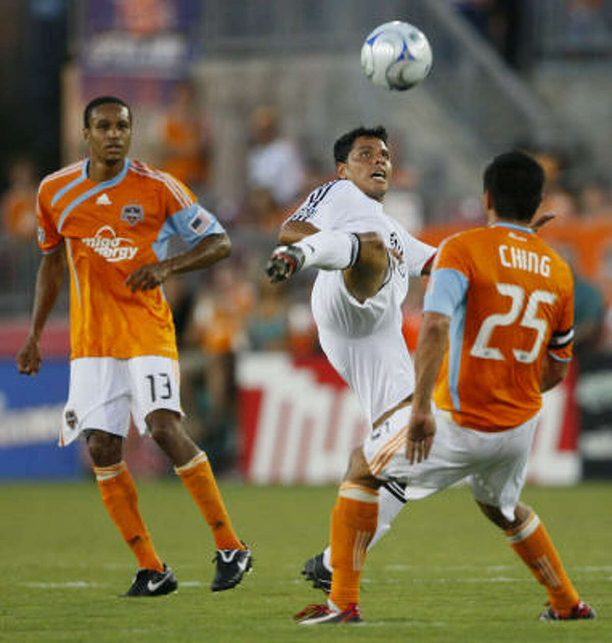 D.C. midfielder Christian Gomez, center, tries to put a foot on a high ball as he's flanked by Ching, right, and Dynamo midfielder Ricardo Clark during the first half.