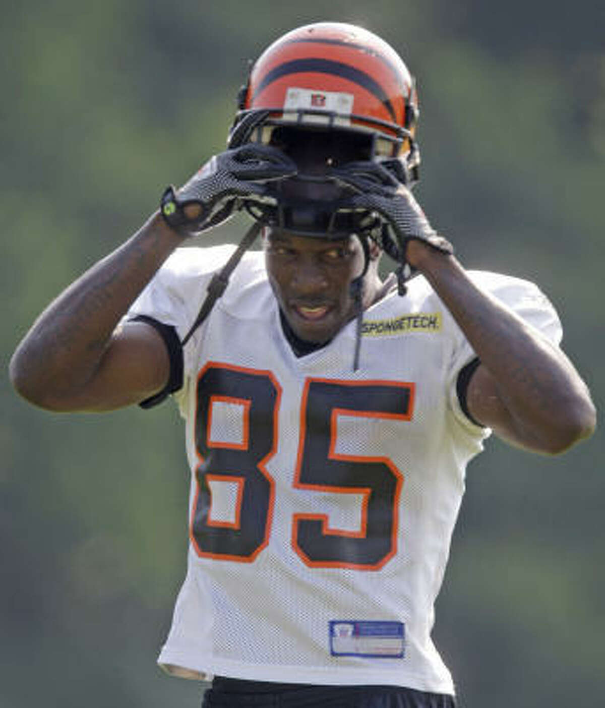 Cincinnati Bengals Bengals receiver Chad Ochocinco puts on his helmet on Saturday, the opening day of his team's camp in Georgetown, Ky.
