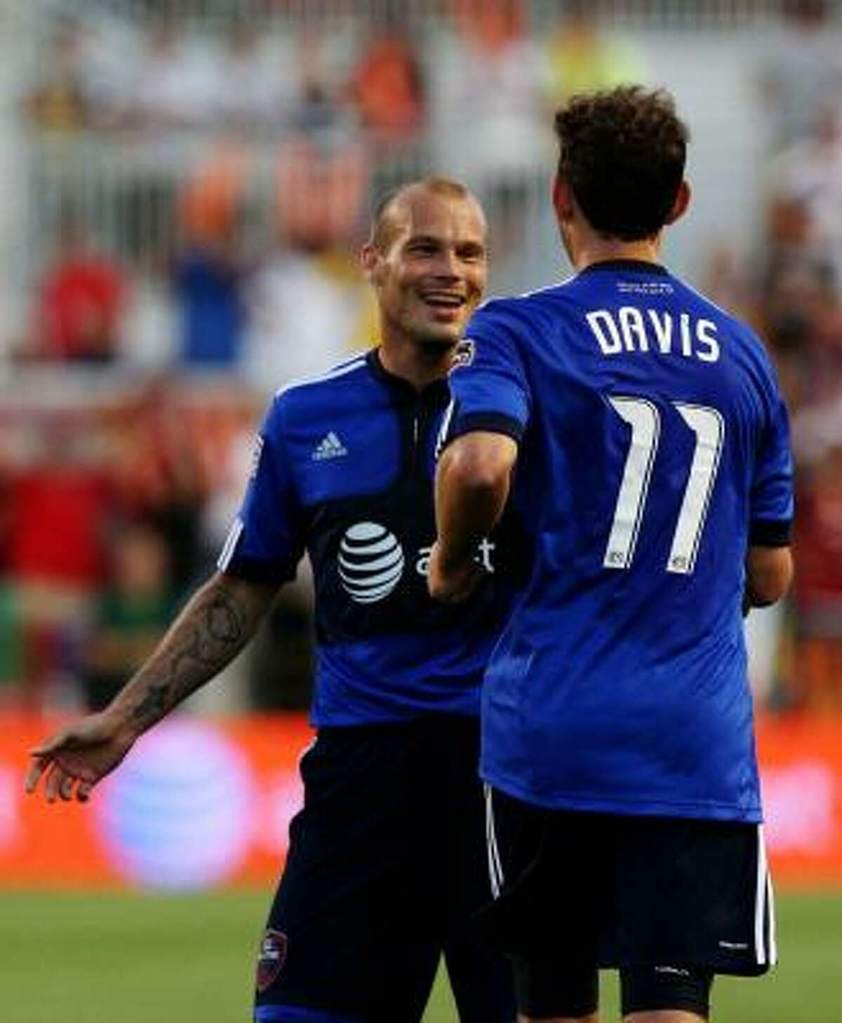 Midfielder Freddie Ljungberg celebrates with Dynamo midfielder Brad Davis after Davis scored the game-tying goal in the first half.