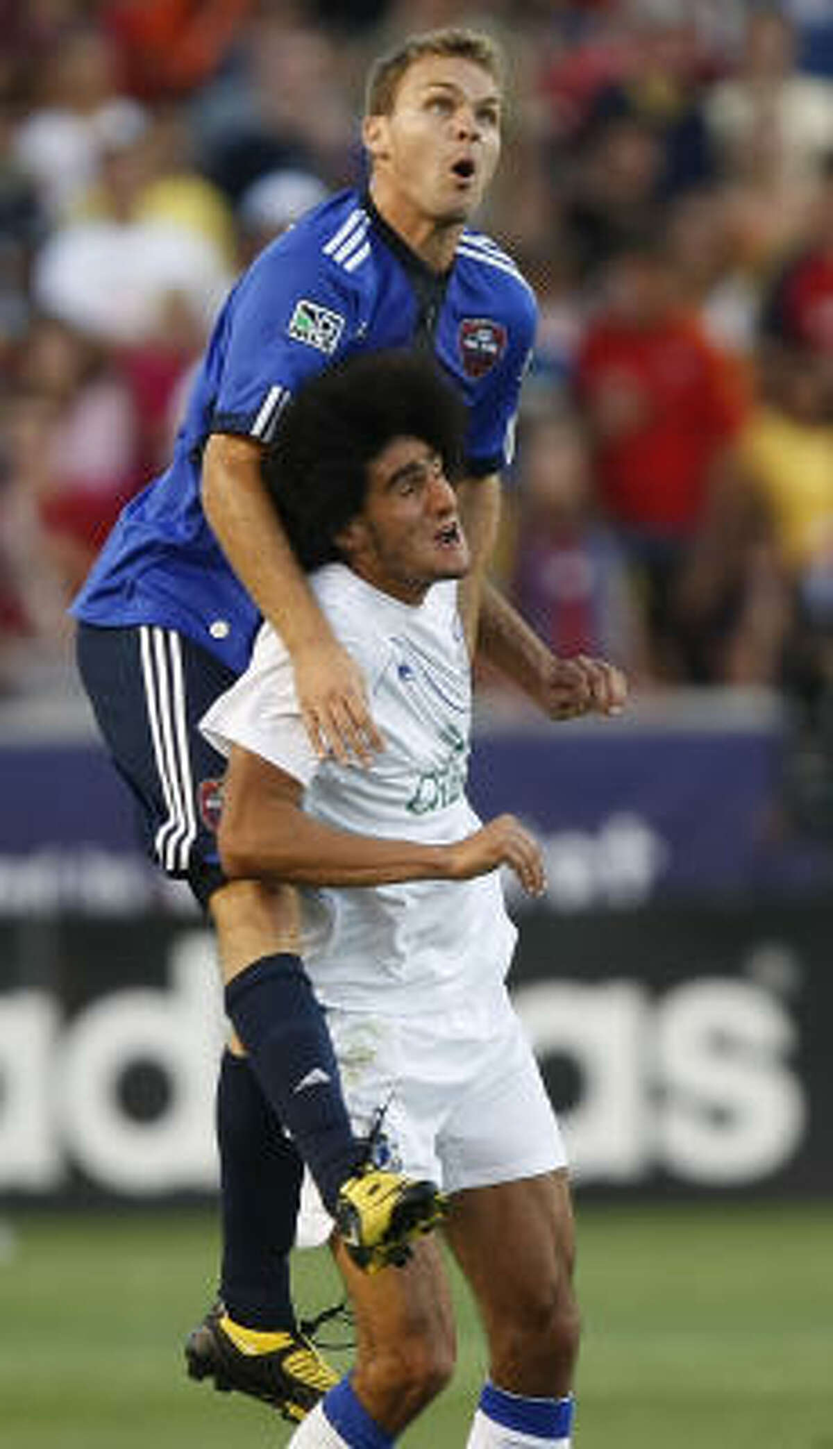 MLS All-Star and Dynamo defender Chad Marshall, left, climbs the back of Everton FC's Marouane Fellaini in the first half.