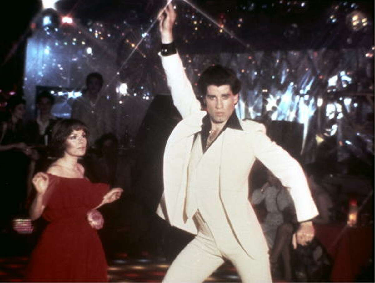 John Travolta struck this iconic pose in a white polyester suit on the disco dance floor in 1977's megahit movie Saturday Night Fever.