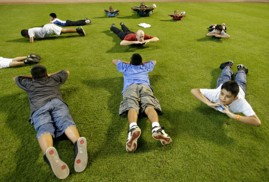 Keep kids' minds active by keeping their bodies active.Kids need at least 30 minutes of physical activity a day. Here, Astros Assistant Athletic Trainer Rex Jones leads a group of kids from the Boys and Girls Club through some stretching exercises. Photo: Karen Warren, Houston Chronicle