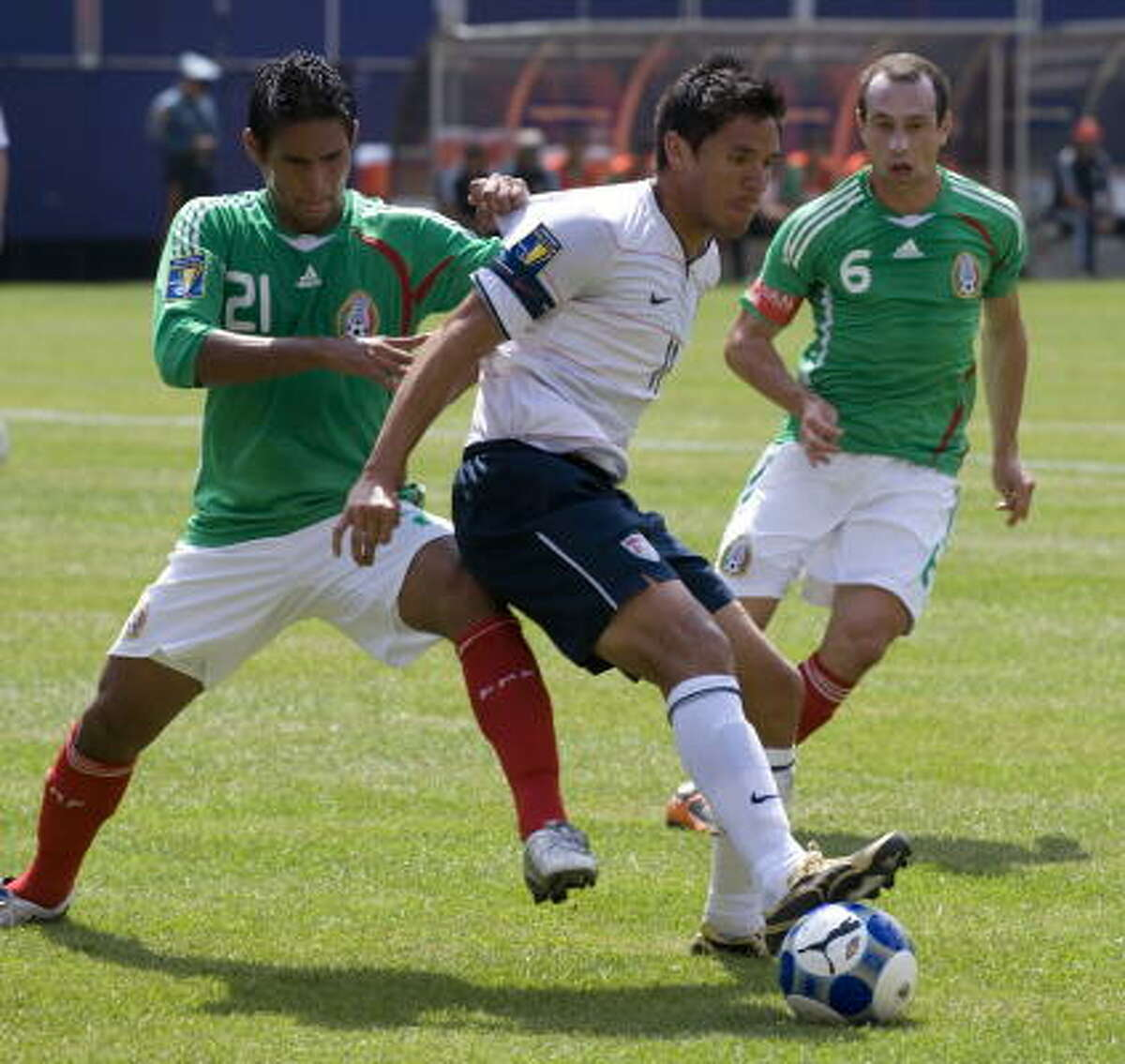 Brian Ching (center) of the United States battles with Mexico's Juan Carlos Valenzuela (left) and Gerardo Torrado (right).