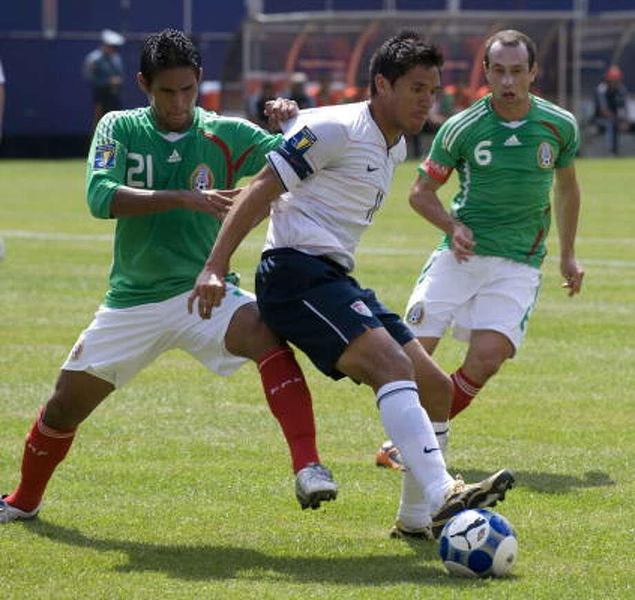 Brian Ching (center) of the United States  battles with Mexico's Juan Carlos Valenzuela (left) and Gerardo Torrado (right). Photo: DON EMMERT, AFP/Getty Images