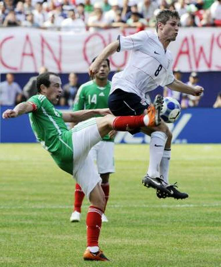 Mexico's Gerardo Torrado, left, and the United States' Logan Pause battle for the ball. Photo: Bill Kostroun, AP