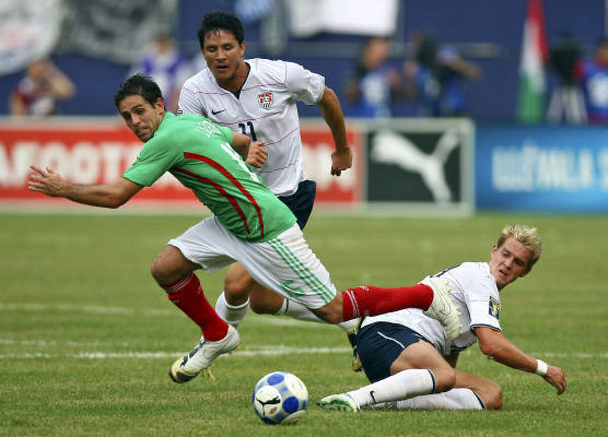 Mexico's Jose Antonio Castro, left, battles for the ball with the United States' Brian Ching, center, and Stuart Holden.