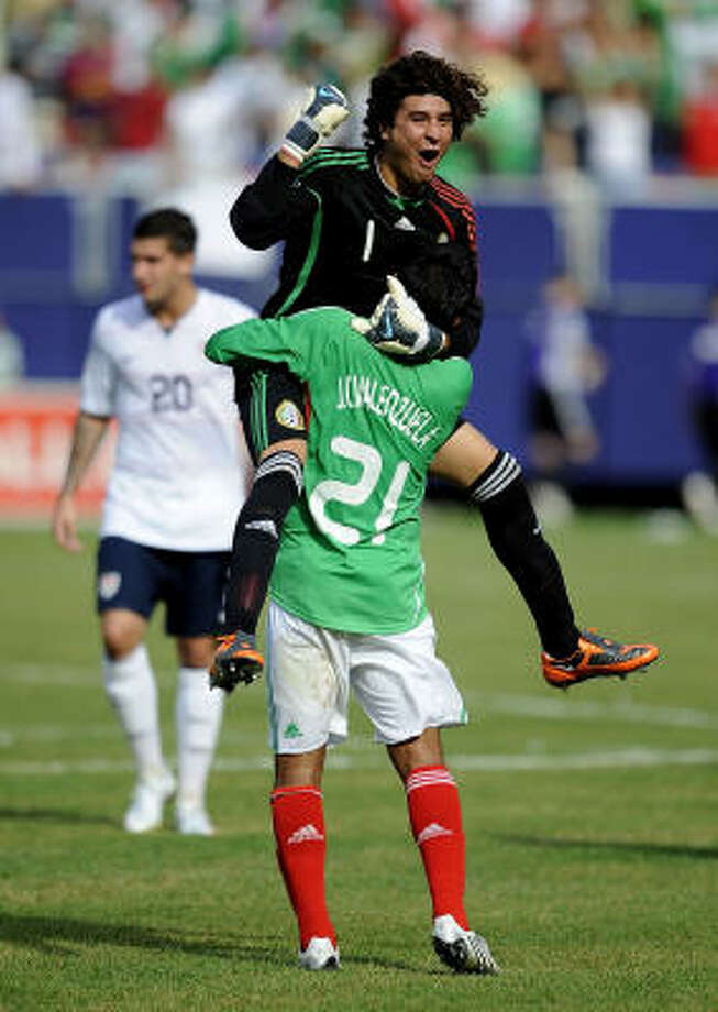 Goalkeeper Guillermo Ochoa (1) and Juan Carlos Valenzuela (21) of Mexico celebrate 5-0 win over the United States. Photo: Jeff Zelevansky, Getty Images