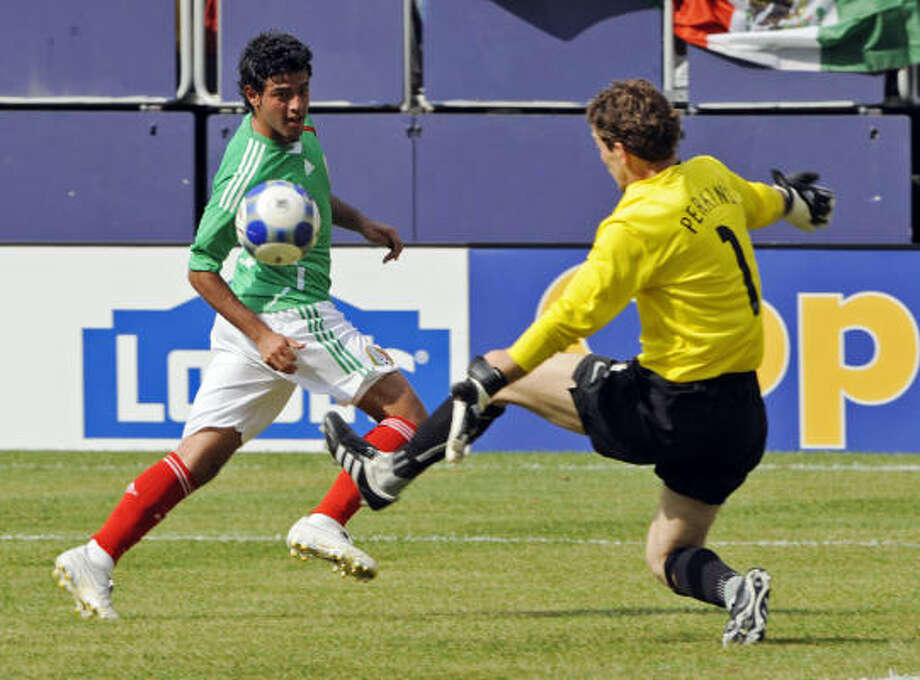 Mexico's Carlos Vela, left, scores his team's third goal past United States goalkeeper Troy Perkins. Photo: Bill Kostroun, AP