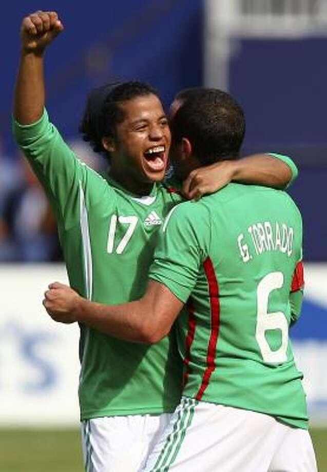 Mexico's Giovani Dos Santos (17) and Gerardo Torrado, right, embrace as they celebrate during Mexico's win. Photo: Mel Evans, AP