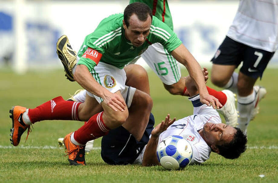 Gerrardo Torrado (6) of Mexico collides with Brian Ching (11) of the United States. Photo: Jeff Zelevansky, Getty Images